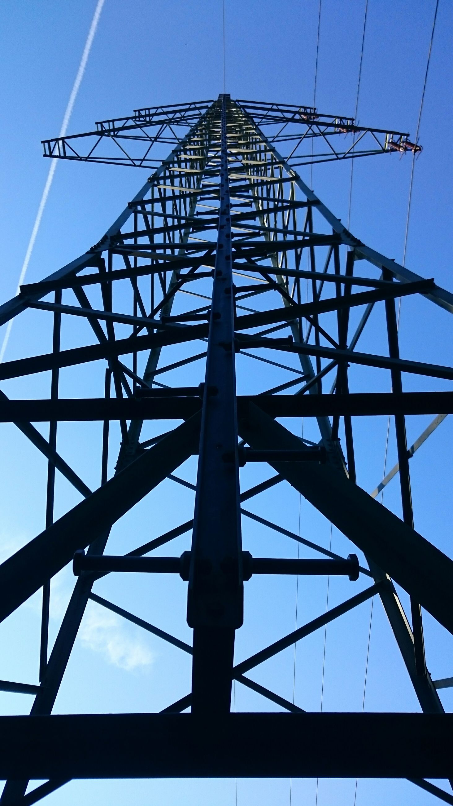 low angle view, connection, power line, electricity pylon, clear sky, electricity, built structure, power supply, cable, sky, silhouette, blue, architecture, metal, technology, fuel and power generation, outdoors, no people, engineering, day