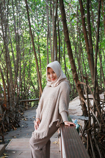 Portrait of smiling woman in hijab while standing on footbridge in forest