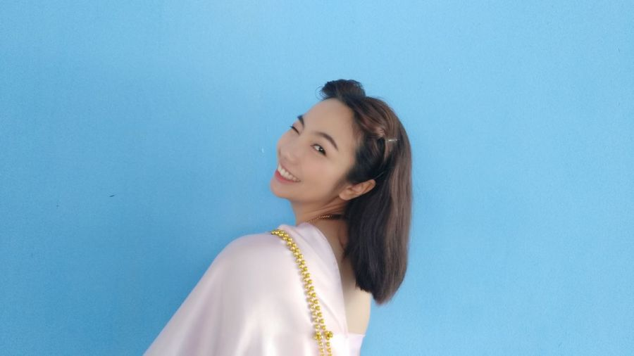 Side view portrait of smiling young woman winking against blue background