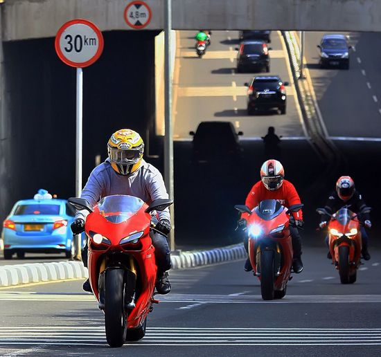 People riding motorcycles on road