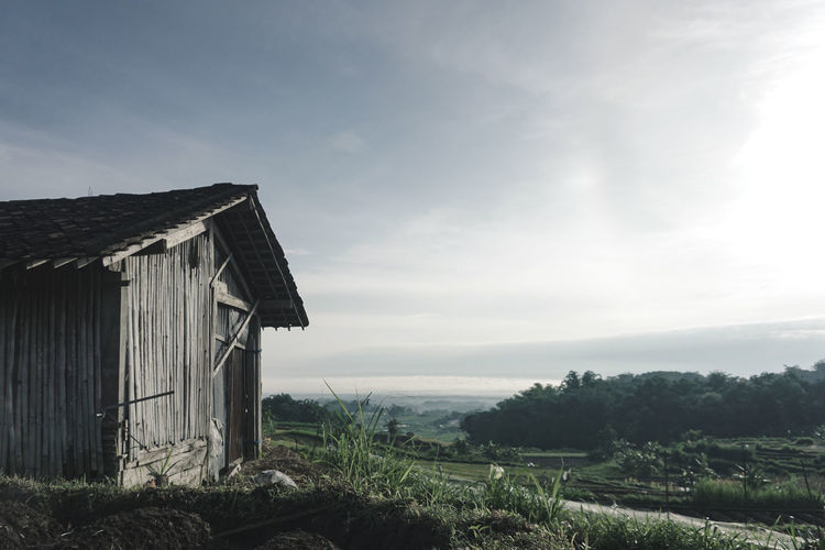 Scenic view of field against sky and a little shack