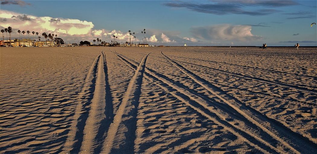 Tire tracks on sand at beach against sky