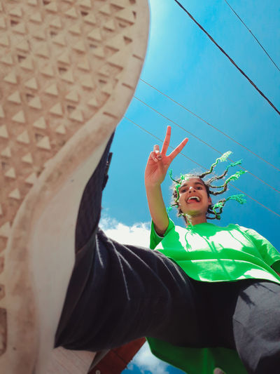 Low angle portrait of cheerful young woman with braided hairstyle against sky