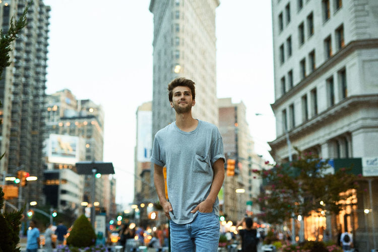 Portrait of smiling young man standing against cityscape