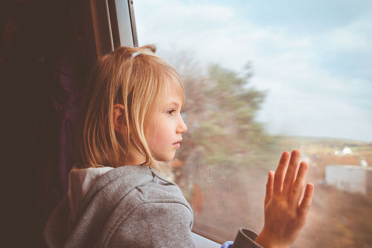 Close-Up Of Girl Looking Through Train Window