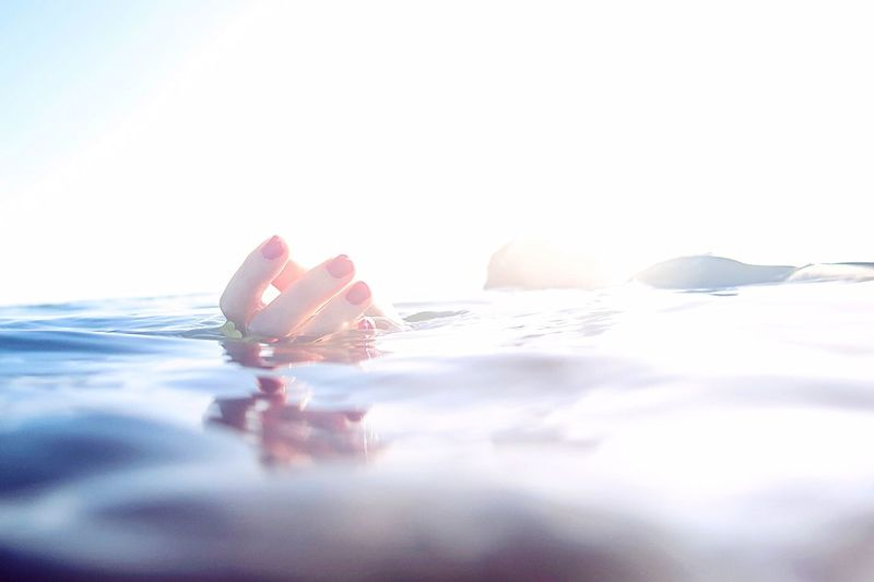 Woman swimming in sea against clear sky