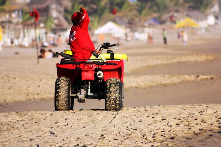 Rear View Of Man On Quadbike At Sandy Beach