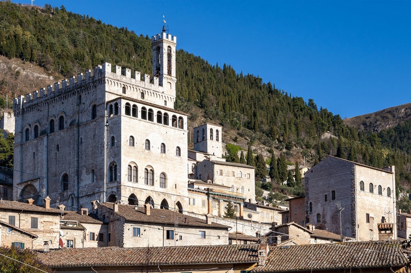 Gubbio, a medieval town in Umbria famous for the beauty of the area and for the events linked to San Francesco, Italy. Palazzo dei Consoli. Culture Famous Gubbio Italy Medieval Renaissance Ancient Arch Architecture Art Beautiful Blue Classic Colorful Creams Decorations Door Green Hill Historical History Humanism Nature Ocher Orange Outdoor Painting Quiet Sky Travel Umbria Urban Landscape Vacation Village White Window Yellow