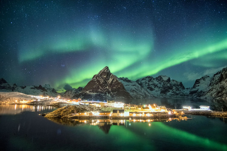 Aurora borealis over mountains in scandinavian village glowing at Sakrisoy, Lofoten, Norway Night Mountain Scenics - Nature Illuminated Beauty In Nature Sky Star - Space Reflection Winter Water Tranquil Scene Cold Temperature No People Mountain Range Snow Tranquility Green Color Nature Astronomy Snowcapped Mountain Aurora Polaris Lofoten Norway Scandinavia Winter