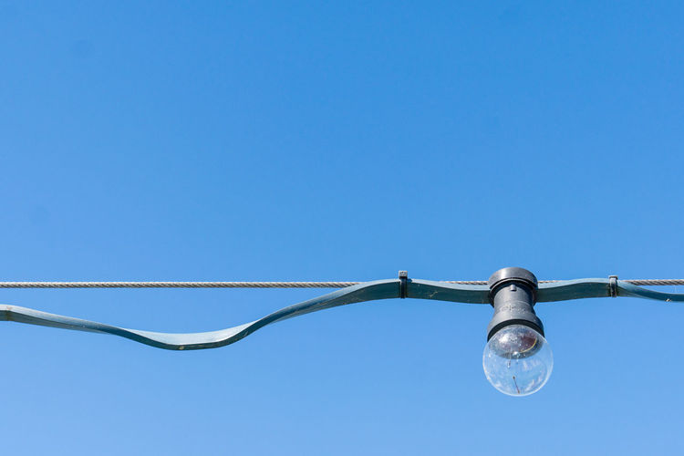 Light bulb hanging on wire against clear blue sky