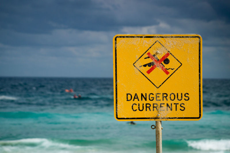 Close-up warning sign against sea