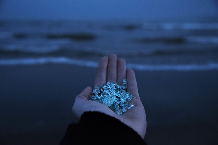 Cropped hand holding crystals at beach during dusk