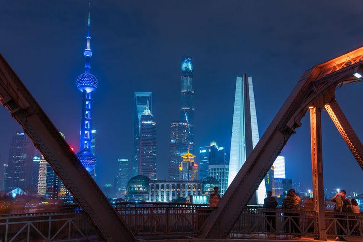 Illuminated Skyscrapers Seen From Bridge In City At Night