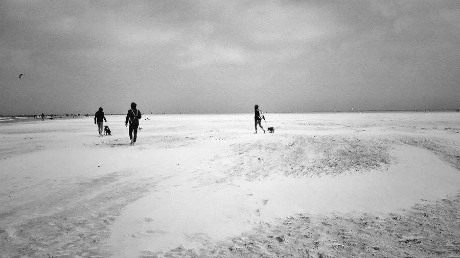 People Walking On Snow Covered Beach Against Cloudy Sky