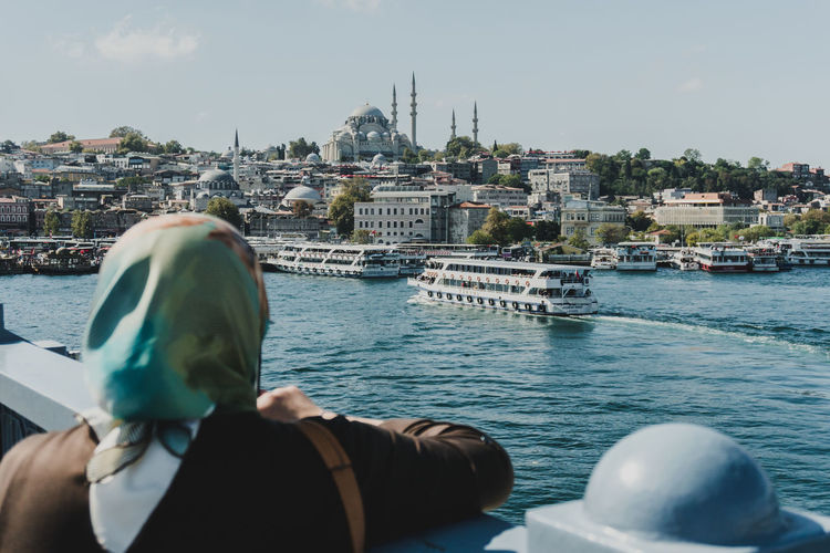 A woman in traditional muslim dress overlooks the river and a mosque in Istanbul. - IG: @LostBoyMemoirs (All photos taken on Sony A6300 and edited in Lightroom). Istanbul Turkey Turkish EyeEm Best Shots The Week on EyeEm Streetwise Photography Streetphotography Street Photography People People Watching people and places Travel Building Exterior Lifestyles Mosque Leisure Activity Cityscape The Art Of Street Photography