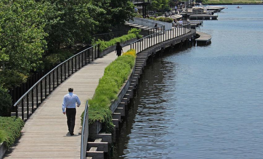 Rear view of man walking on footbridge over milwaukee river