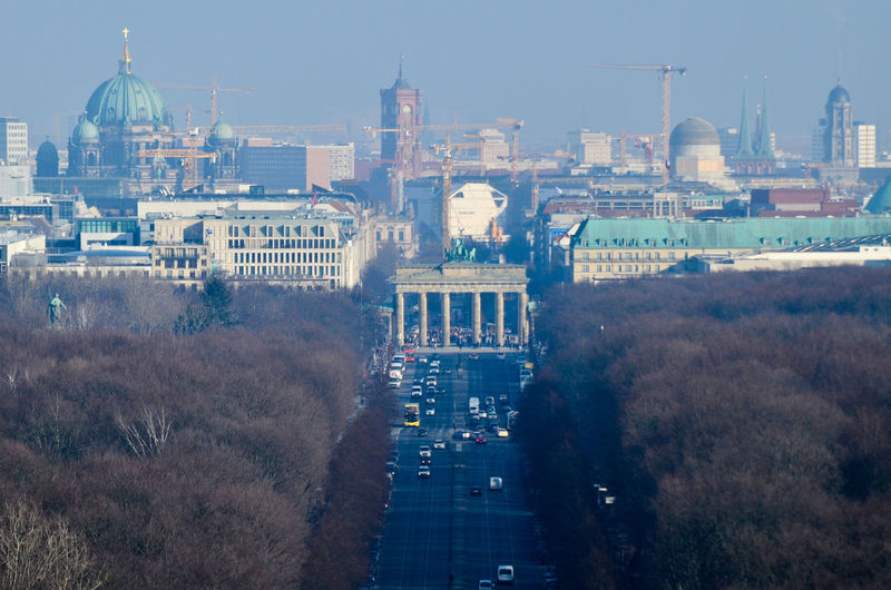 High angle view of road amidst trees leading towards brandenburg gate in city
