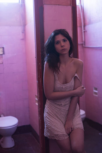 Portrait Of Sensuous Woman Standing In Public Bathroom
