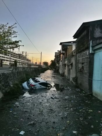 a beautiful disaster Philippines Accident Car Slums Third World Prison Water Sky Architecture Building Exterior Built Structure Street Art Vandalism Horizon Over Water Graffiti Vehicle Abandoned