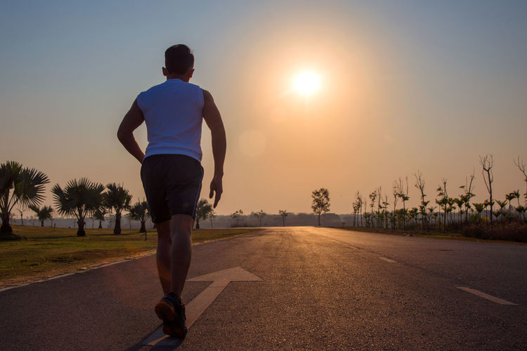 Rear view of man running on road against sky during sunset