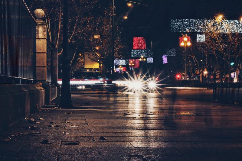 Illuminated street in city at night