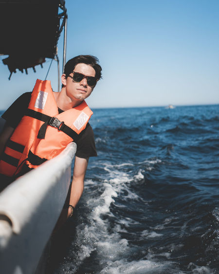 Portrait of man wearing sunglasses and life jacket on boat in sea