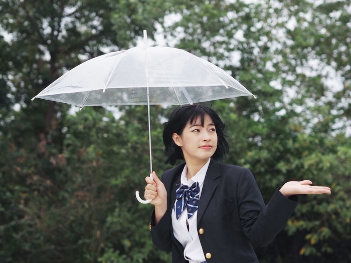 Young woman holding umbrella against trees