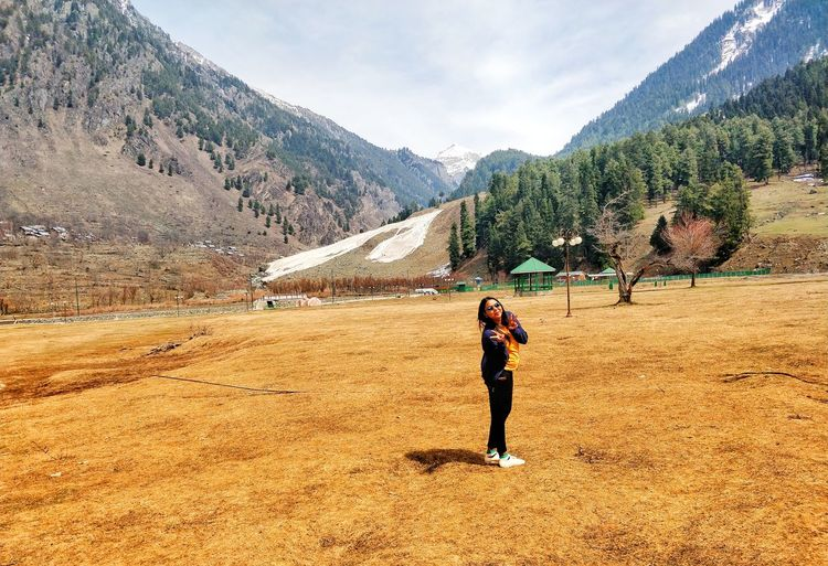 Full length of woman gesturing peace sign while standing on land against mountains
