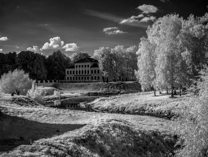 Mid distance view of mansion surrounded by trees against sky at uglich