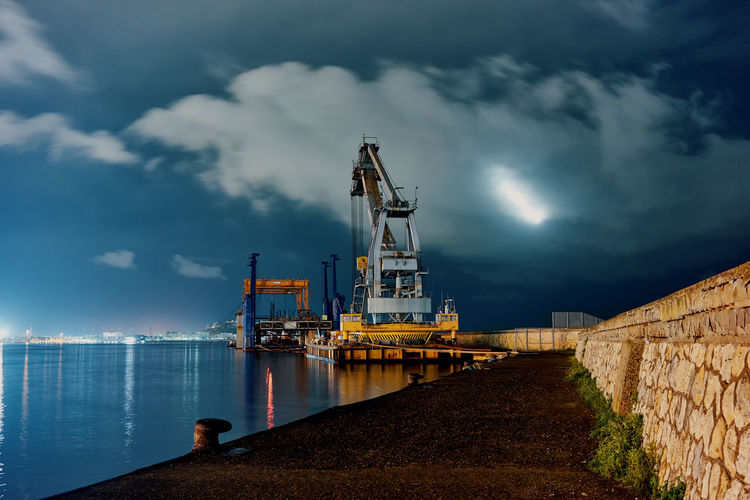Sky Cloud - Sky Industry Water Nature Sea Architecture Nautical Vessel Transportation Outdoors Pier Illuminated No People Built Structure Commercial Dock Machinery Oil Industry Fuel And Power Generation Harbor Industrial Equipment Night Nightphotography Crane Capture Tomorrow