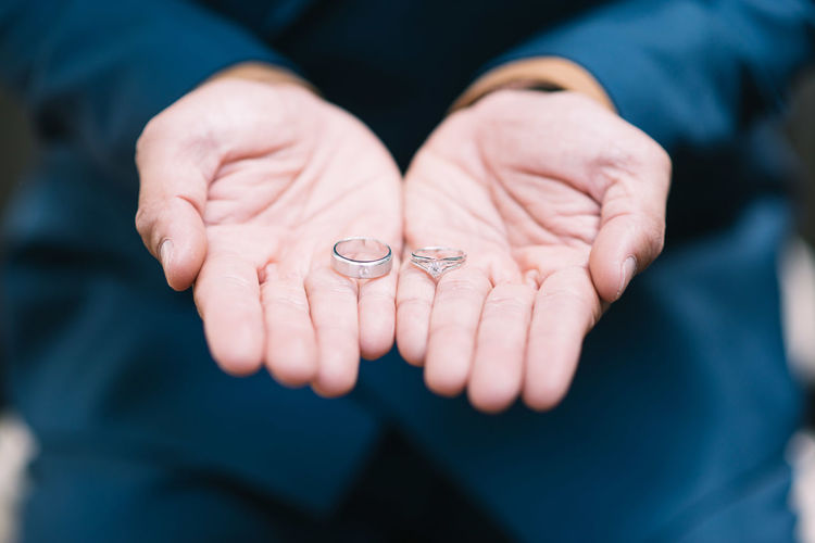 Close-Up Of Man Holding Wedding Rings
