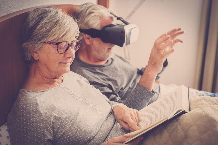 Senior woman reading book while man using virtual reality at home
