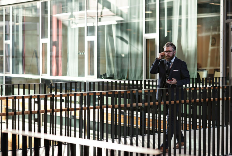 Full length of a man standing by railing