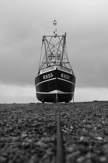 Low angle view of ship moored on shore against sky
