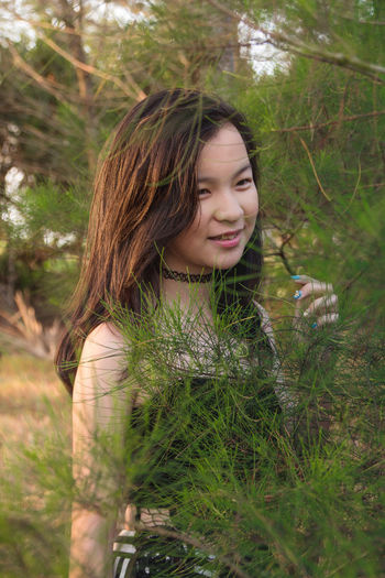 Smiling girl standing by branches