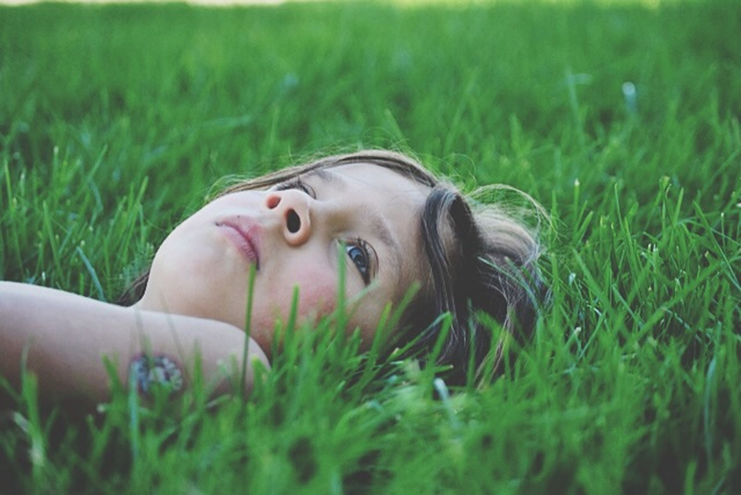 grass, person, field, portrait, young adult, looking at camera, grassy, young women, lifestyles, headshot, leisure activity, relaxation, green color, close-up, focus on foreground, day, head and shoulders