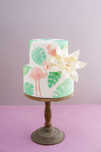 Two tiered tropical wedding cake with fondant, tropical wafer paper leaves and flamingos with a big golden statement flower on wooden cake stand Flamingo Cake Tropical Tropical Wedding Cake Wafer Paper Waferpaper Wedding Cake