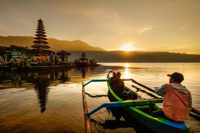 People sitting on boat in lake during sunset