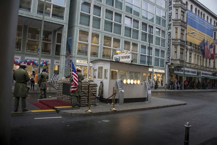 """Checkpoint Charlie (or """"Checkpoint C"""") was the name given by the Western Allies to the best-known Berlin Wall crossing point between East Berlin and West Berlin during the Cold War (1947-1991). GDR leader Walter Ulbricht agitated and maneuvered to get the Soviet Union's permission to construct the Berlin Wall in 1961 to stop Eastern Bloc emigration westward through the Soviet border system, preventing escape across the city sector border from communist East Berlin into free West Berlin. Checkpoint Charlie became a symbol of the Cold War, representing the separation of East and West. (🕵spying on checkpoint charlie🕵) Checkpointcharlie Checkpoint Charlie  Berlin Germany Army US Flag USA FLAG Flag Military Cold War Police Police Officers Policeman Policemen Adult People Streetphotography Street Photography Exceptional Photographs Building Exterior Adults Only Military Uniform Military Police Holiday Vacations Finding New Frontiers Traveling Home For The Holidays Lost In The Landscape"""