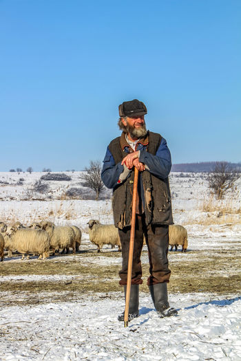 Shepherd Of The Sheep Winter Animal Themes Beauty In Nature Clear Sky Day Domestic Animals Front View Full Length Holding Leisure Activity Lifestyles Mammal Mature Men Nature One Animal One Person Outdoors People Real People Sky Standing Traditional Clothing Warm Clothing