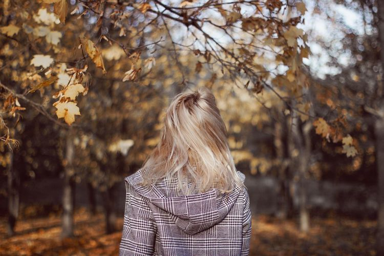 Rear view of woman standing by tree during autumn
