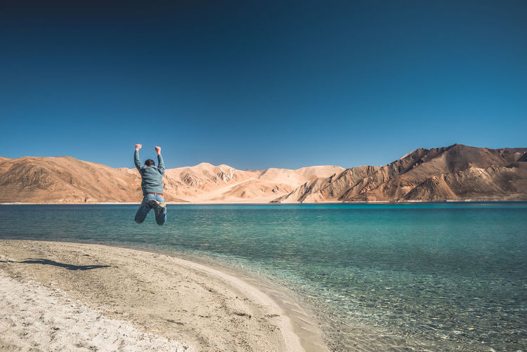 Rear view of man jumping with arms raised by sea against sky