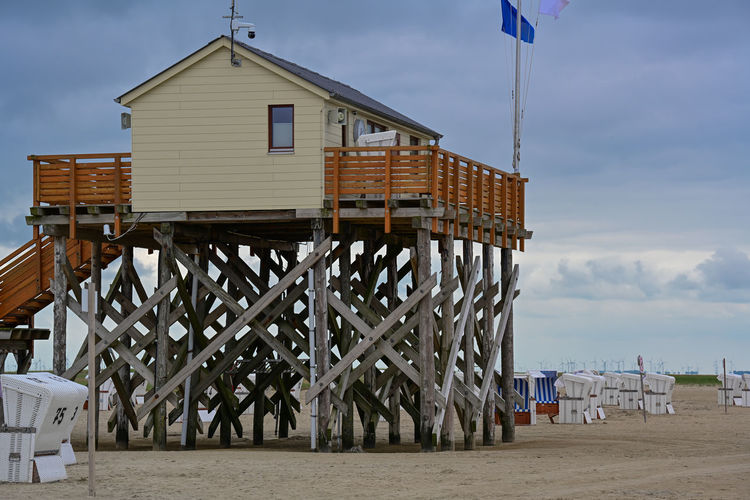 Built structure on beach by sea against sky