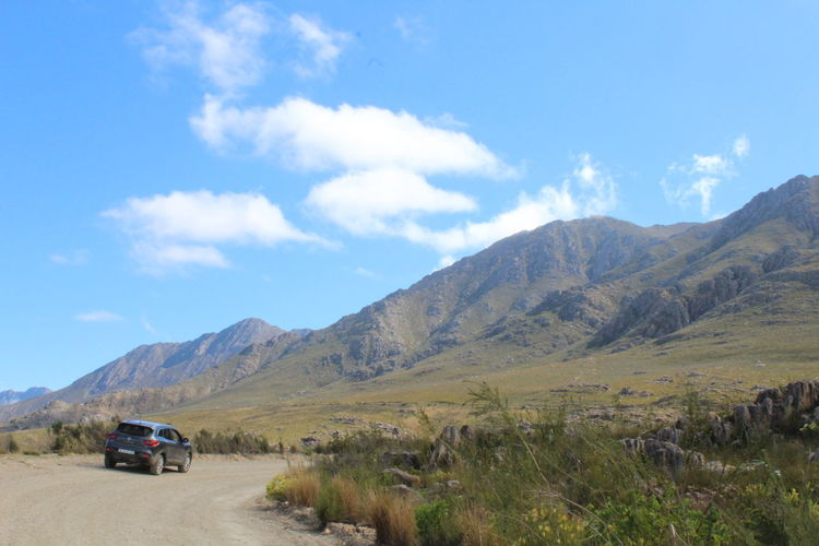 Cars on road by mountains against sky