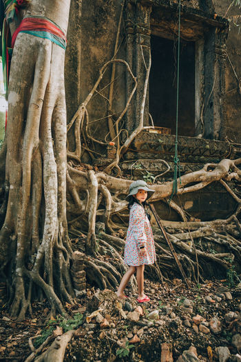 Girl standing by tree trunk