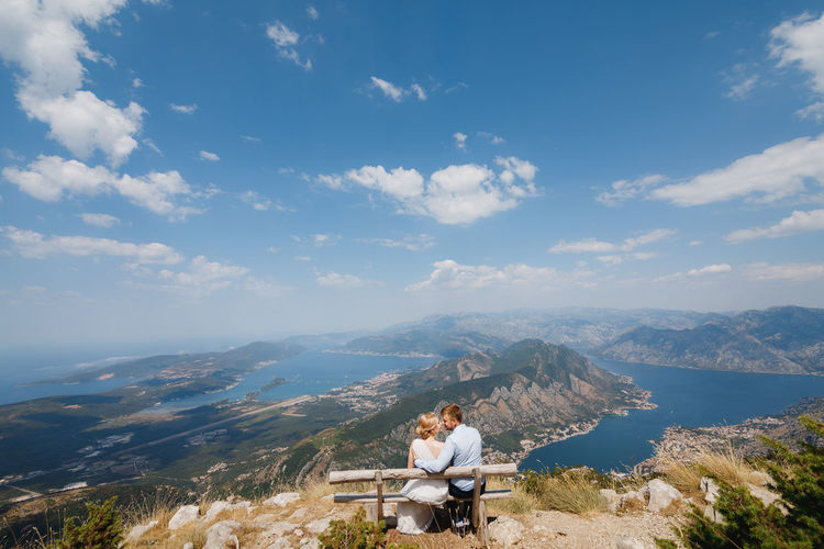 People sitting on mountain against sky
