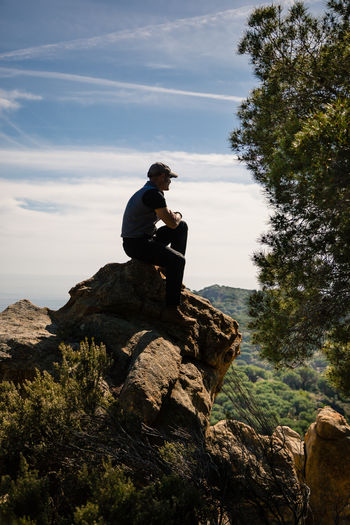 Side view of young man sitting on rock against sky
