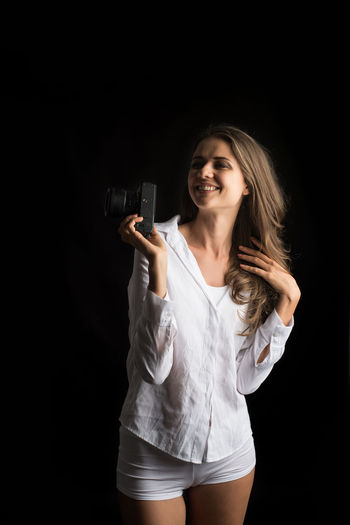 Black Background Studio Shot One Person Young Adult Three Quarter Length Smiling Holding Women Indoors  Front View Hair Communication Gun Young Women Adult Happiness Standing Hairstyle Long Hair Beautiful Woman