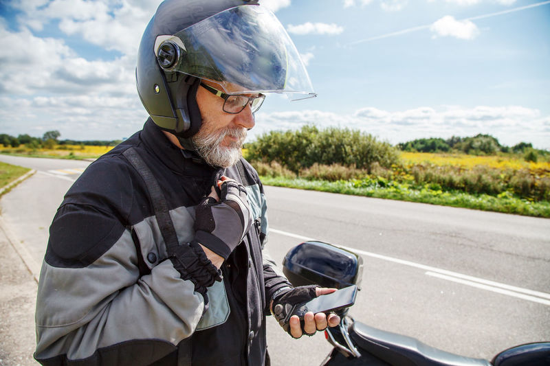 Man by motorcycle using phone on road