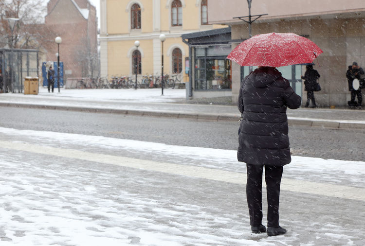 One woman standing with an red umbrella during the snowfall. Umbrella Winter Cold Temperature Snow Real People Women Protection Adult One Person Street Outdoors Snowing City Red Sweden
